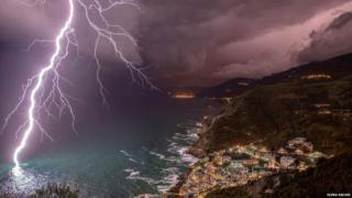 A large bolt of lightning strikes the sea at night by a coastal village