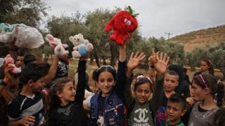 """Suriye'de çocuklar hediyelerinin sevincini yaşarken. Hediyeleri gönderen ise Finlandiya'da yaşayan ve kendisine """"Oyuncak Kaçakçısı"""" ismini takan bir Suriyeli"""