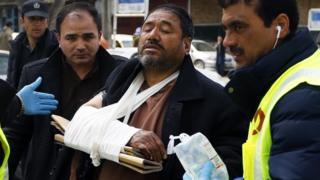 Afghan health workers carry a wounded man from a hospital after gunmen attacked a political gathering in Kabul, Afghanistan, 06 March 2020