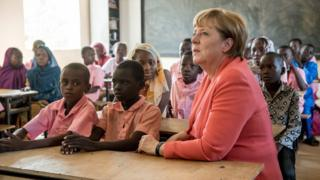 German Chancellor Angela Merkel (R) speaks with primary school students from the Goudell II. school in Niamey, Niger, on 10 October 2016