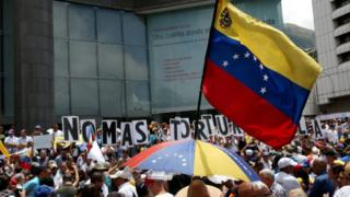 """Bandera de Venezuela y detrás unos carteles que dicen """"No más torturas""""."""