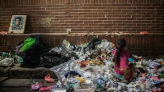 Una niña escarbando entre la basura