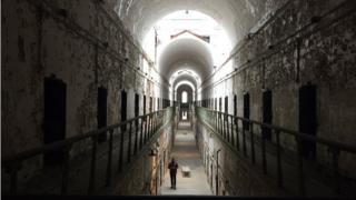 Russell Craig walks a cell block after hours