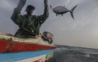 Senegalese fisherman Modu Samba catches a fish in the Atlantic Ocean off the 400 year old fishing village of Ngor, near Dakar, 26 February 2019.