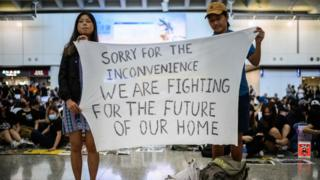 """Hong Kong activists at an airport rally hold a banner reading: """"Sorry for the inconvenience we are fighting for the future of our home"""", 9 August 2019"""