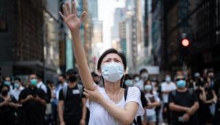 A woman raises her hand while wearing a mask on Friday in Hong Kong
