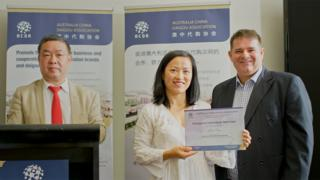 An Australia-based daigou receives her membership certificate from the Australia China Daigou Association