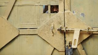 A man peeks through an opening of a door to a prison ward during a concert at the Tihar jail in New Delhi on April 26, 2012.