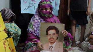 Imdad Ali's wife, her face mostly covered, holds a photo of her husband