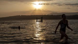 People enjoy bathing at sunrise in the Geneva lake in Geneva, Switzerland
