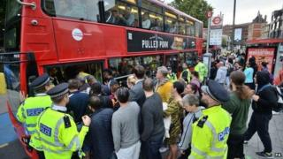 People try to board a bus in Stratford