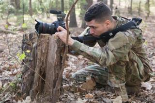 A soldier competes in the 5th annual Hilda Clayton Best Combat Camera Competition in April 2017