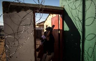 Sarkaal kamid ah Booliiska Koonfur Afrika oo hortaagan dukaan la bililiqaystay oo kuyaal magaalada Soweto.