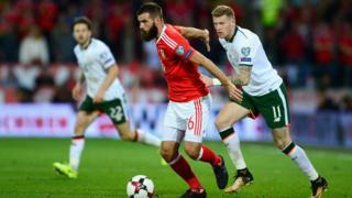 Joe Ledley of Wales holds off James McClean of the Republic of Ireland