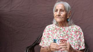 María Teresa Jimenez holds up photographs of her children