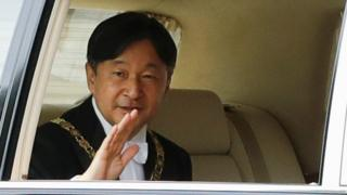 Emperor Naruhito waves from his car