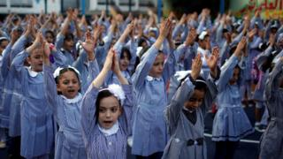 Palestinian school girls raise their hands during a morning exercise at a Unrwa-run school, in Gaza City, on 29 August 2018