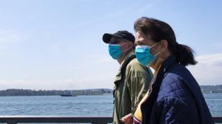 People in masks walk along New York Harbor in New Yor