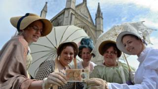 Jane Austen fans in costume pose with the new £10 note in front of Winchester Cathedral where the author is buried