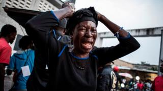 One woman wey wear black as she dey cry for her family wey die. January 2017