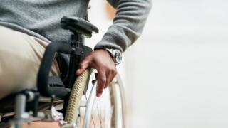 Homem empurra cadeira de rodas