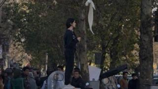beyaz başörtüsünü bir sopaya asarak, İslamcı iktidara karşı duruş ortaya koyan kadın