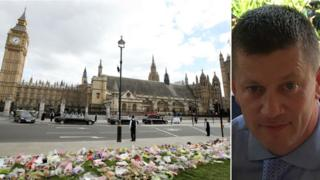 Flowers left outside the Houses of Parliament in honour of PC Keith Palmer and picture of PC Keith Palmer