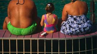 Una niña entre dos personas gordas