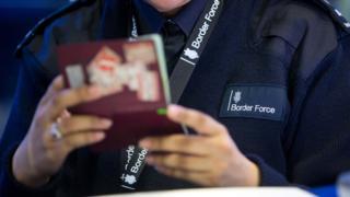 Border Force officer holding passport