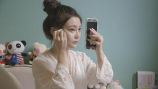 Lele Tao puts on make-up in her night gown.
