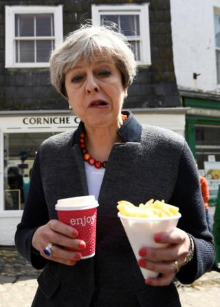 Prime Minister Theresa May enjoys some chips during a campaign stop in Mevagissey, Cornwall, 2 May 2017.