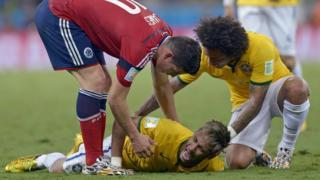 Neymar está en el suelo quejándose de dolor y sus compañeros intentan incorporarlo.