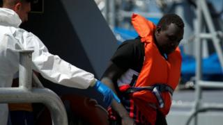 A migrant disembarks from an Armed Forces of Malta vessel after arriving at its base in Marsamxett Harbour, Valletta