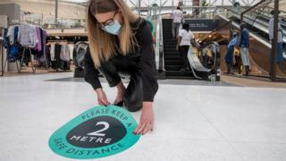 Woman wearing face mask sticks social distancing sticker to John Lewis floor