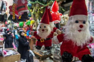 People walk near Santa Claus toys displayed for sale for Christmas and new year in Cairo, Egypt, 25 December 2018