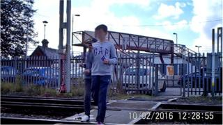 Children on the rail crossing on their mobile phones