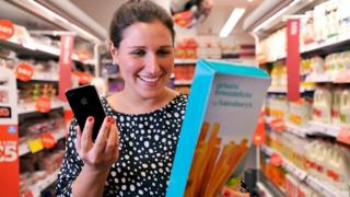 A shopper holding a mobile phone and breadsticks