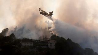 A firefighting aircraft attmpts to douse the forest fire in Carros near Nice, southern France, 24 July 2017.