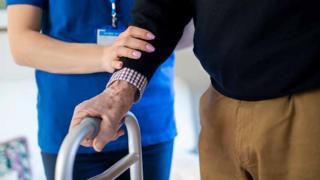 nurse helps elderly man holding frame