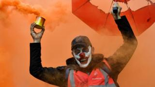 A man wearing a clown mask and waving a smoke bomb takes part in a demonstration to protest against the pension overhauls, in Marseille, southern France, on 5 December, 2019.