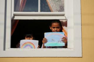 in_pictures Two children stand at the window holding their drawing of what they miss most - their illustrations show rainbows and ice-cream vans.