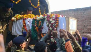Mourners touch the coffin as they take part in the funeral procession for Indian Central Reserve Police Force trooper Mahesh Kumar Meena at Meja village, near Allahabad