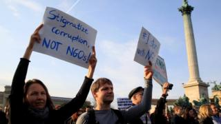 People hold placards during a protest against a new law that would undermine Central European University in Budapest on 15 April