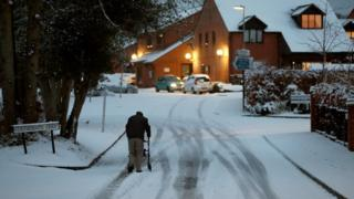 An elderly resident makes his way up a snow covered road