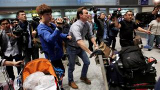 Rupert Wingfield-Hayes, pushing an airport trolley, surrounded by reporters and camera operators in the arrivals hall of Beijing International Airport