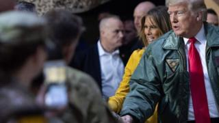 """特朗普身穿绿色外衣、佩带着写有""""三军统帅""""名牌,与驻伊拉克美军握手。"""