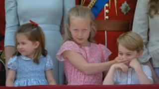Savannah, the Queen's great-granddaughter and daughter of Peter and Autumn Philips, covers Prince George's mouth