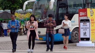 """Des volontaires participent à une campagne contre le """"phubbing"""" dans la zone touristique de Fuling, en Chine."""