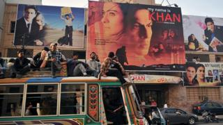 Pakistani commuters, sitting on top of a bus, pass by a cinema screening Indian Bollywood actor Shah Rukh Khan's film 'My Name is Khan' in Karachi on February 12, 2010.