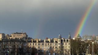 A rainbow over dark skies